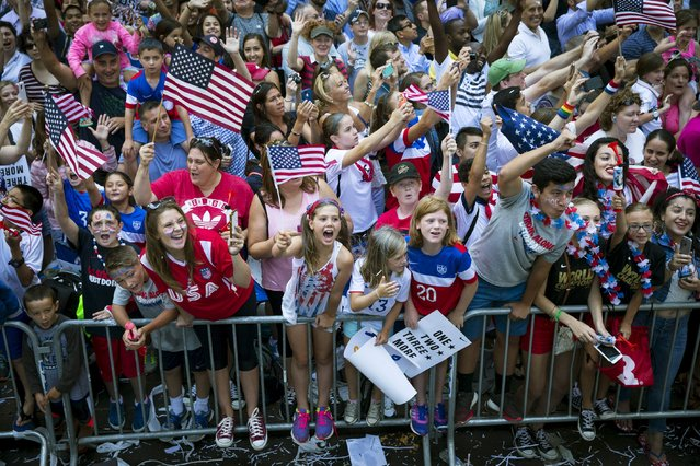 Fans cheer as the U.S. women's soccer team ride past in floats during the ticker tape parade up Broadway in lower Manhattan to celebrate their World Cup final win over Japan in New York, July 10, 2015. (Photo by Mike Segar/Reuters)