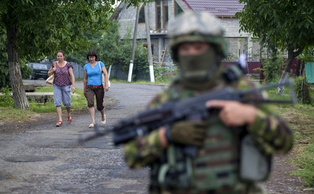 Women walk towards a Ukrainian government serviceman searching for members of Right Sector in the village of Bobovyshche near Mukacheve, Ukraine, July 13, 2015. Kiev has called on Right Sector, which played a prominent role in protests that toppled Moscow-backed President Viktor Yanukovich a year ago, to lay down their weapons after a shootout on Saturday in the town of Mukacheve killed at least two people. (Photo by Reuters/Stringer)