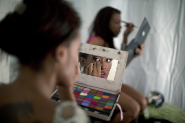 Samba dancer Diana Prado looks in a makeup mirror as applies makeup before the start of a carnival parade at central station in Rio de Janeiro, Brazil, Saturday, February 2, 2013. Prado made her Carnival debut at age 19, after auditioning for a spot with the Sao Clemente, one of 13 top-tier schools that will compete for the annual titles at the Sambadrome this weekend. (Photo by Felipe Dana/AP Photo)