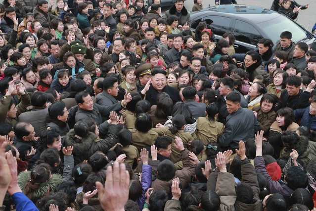 North Korean leader Kim Jong Un (C) smiles as a huge crowd surrounds him while he gives field guidance at the Kim Jong Suk Pyongyang Textile Mill in this undated photo released by North Korea's Korean Central News Agency (KCNA) in Pyongyang December 20, 2014. (Photo by Reuters/KCNA)