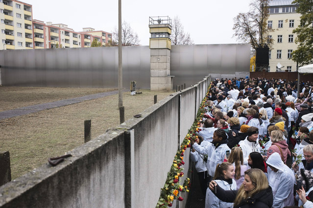 People stuck flowers in remains of the Berlin Wall during a commemoration ceremony to celebrate the 30th anniversary of the fall of the Berlin Wall at the Wall memorial site at Bernauer Strasse in Berlin, Saturday, November 9, 2019. (Photo by Markus Schreiber/AP Photo)