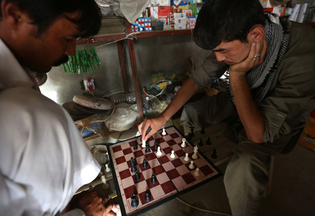 Afghan men play a game of chess in a shop on the outskirts of Kabul, Afghanistan, Saturday, July 25, 2015. (Photo by Rahmat Gul/AP Photo)
