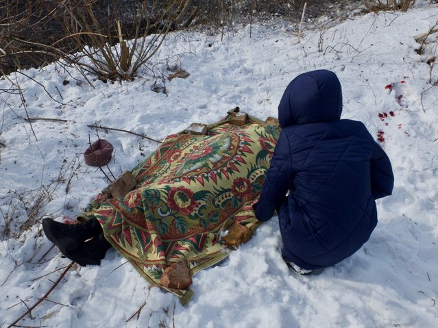 Nadia Volkova leans over the body of her mother, Katya, who was killed during shelling in the eastern Ukrainian city of Avdiyivka on February 1, 2017. War returned with a fury four days ago to the eastern Ukrainian city of Avdiyivka. On February 1, around 7:30 a.m., a salvo of rockets rained down on the city of 22,000, residents say. Katya Volkova, 60, a mother and grandmother, was killed on the road from her house as she walked to the market. (Photo by Cristopher Miller/Radio Free Europe/Radio Liberty)