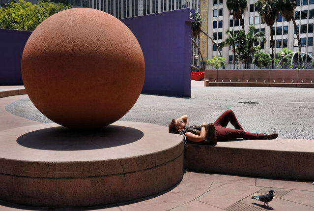 A woman suns herself in an empty park in downtown Los Angeles on Friday, June 3, 2016. A heat wave in large parts of the West and Southwest has many scattering for reprieve from the sun. (Photo by Richard Vogel/AP Photo)