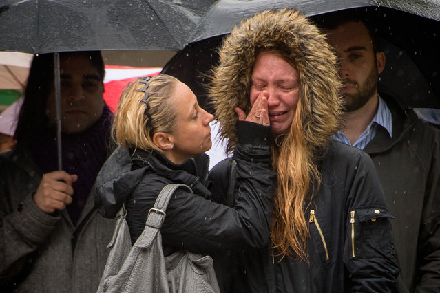 A woman cries at a flower memorial after a moment of silence to remember the victims of Saturday's attacks in the London Bridge area of London on Tuesday, June 6, 2017. A new search was underway Tuesday in a neighborhood near the home of two of the London Bridge attackers, hours after police said they had freed everyone detained in the wake of the Saturday evening rampage that left several dead and dozens wounded. (Photo by Dominic Lipinski/PA Wire)