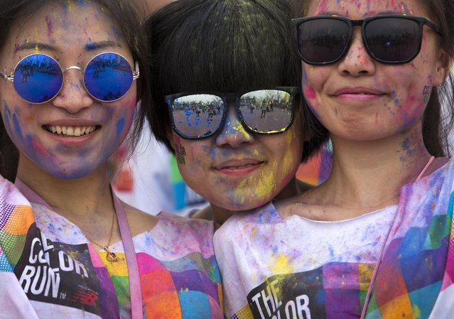 Participants with color powder on their face and shirt pose for a photo after they take part in a five-kilometer color run event in Beijing, China Saturday, June 21, 2014. (Photo by Andy Wong/AP Photo)