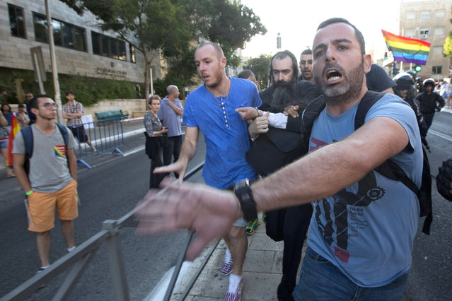Plainclothes Israeli police detain an-ultra Orthodox Jew after he attacked people with a knife during a Gay Pride parade Thursday, July 30, 2015 in central Jerusalem. (Photo by Sebastian Scheiner/AP Photo)