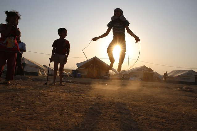 Children, who fled from violence in Mosul, play during sunset inside the Khazer refugee camp on the outskirts of Arbil, in Iraq's Kurdistan region, June 27, 2014. Grand Ayatollah Ali Sistani, the most influential Shi'ite cleric in Iraq, called on the country's leaders on Friday to choose a prime minister within the next four days, a dramatic political intervention that could hasten the end of Nuri al-Maliki's eight year rule. (Photo by Ahmed Jadallah/Reuters)