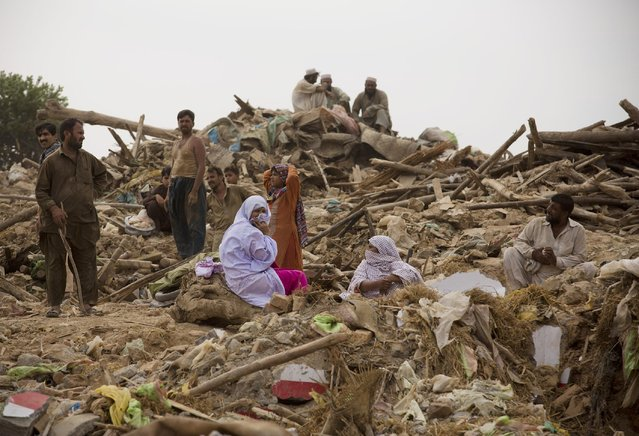 Residents sit on their belongings after their houses were bulldozed by the government, in Islamabad, Pakistan, Friday, July 31, 2015. Authorities demolished illegal mud houses of Afghan refugees and Pakistani tribal people who fled their villages due to ongoing crackdown operations against militants. People were injured during clashes between police and residents. (Photo by B. K. Bangash/AP Photo)