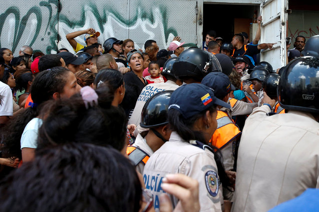 People gather to try to buy pasta while riot police try to control the crowd outside a supermarket in Caracas, Venezuela, June 10, 2016. (Photo by Carlos Garcia Rawlins/Reuters)