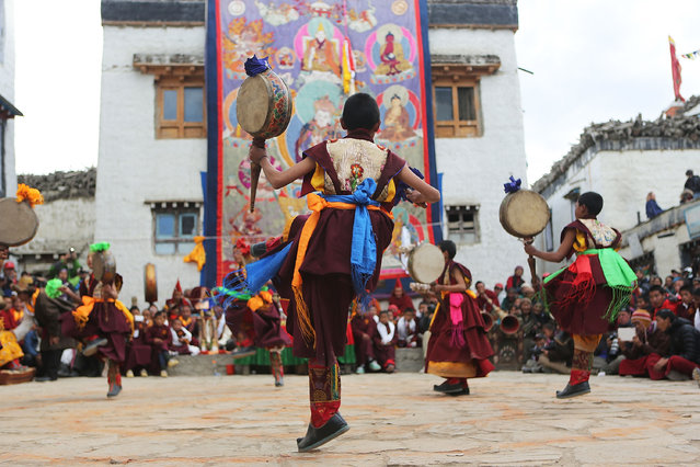 Young monks perform a ceremonial dance with nga, Tibetan drums, during the Tenchi Festival on May 26, 2014 in Lo Manthang, Nepal. The Tenchi Festival takes place annually in Lo Manthang, the capital of Upper Mustang and the former Tibetan Kingdom of Lo. Each spring, monks perform ceremonies, rites, and dances during the Tenchi Festival to dispel evils and demons from the former kingdom. (Photo by Taylor Weidman/Getty Images)
