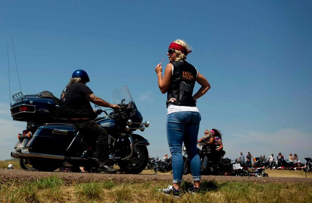 Stephanie Beaver, of Oklahoma, watches bike traffic come in to the Stone House Saloon outside of Belle Fourche, South Dakota, while participating in the annual Sturgis Motorcycle Rally in South Dakota, August 5, 2015. (Photo by Kristina Barker/Reuters)