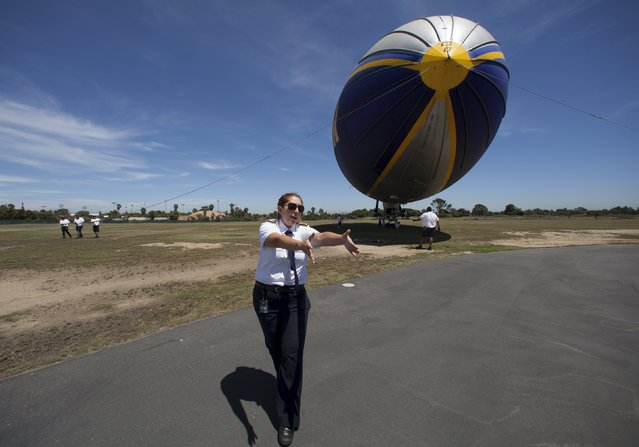 "One of only three active female blimp pilots in the world, Kristen Arambula guides her passengers towards the Goodyear blimp ""Spirit of America"" in Carson, California August 5, 2015. (Photo by Mike Blake/Reuters)"