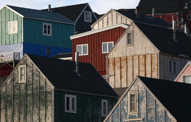 Houses are illuminated by the early morning sun in the town of Tasiilaq in eastern Greenland. (Photo by Bob Strong/Reuters)