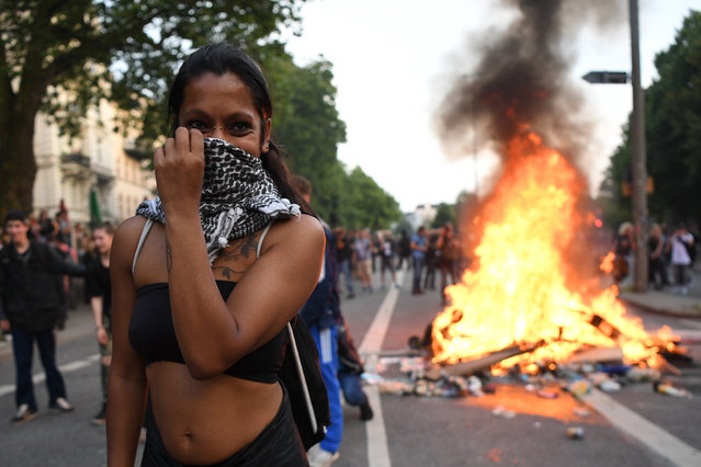 A woman covers her face as a fire burns in the middle of town during an anti-G20 protest on July 7, 2017 in Hamburg, Germany. Authorities are braced for large-scale and disruptive protests as Leaders of the G20 group of nations arrive in Hamburg for the July 7-8 G20 summit. (Photo by Leon Neal/Getty Images)