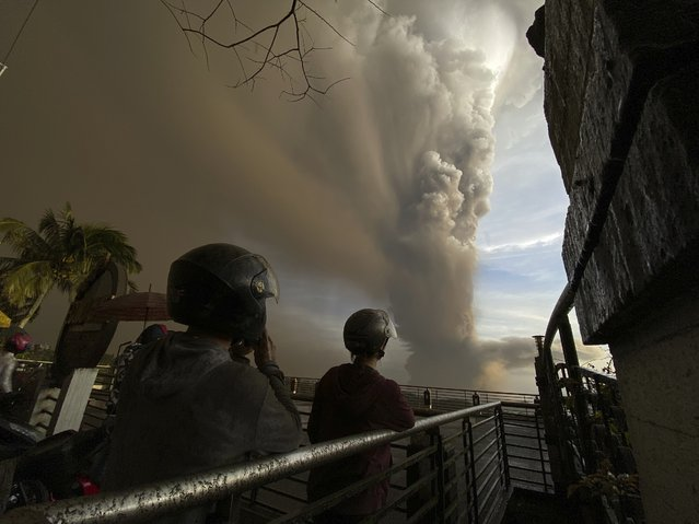 People watch plumes of smoke and ash rise from as Taal Volcano erupts Sunday January 12, 2020, in Tagaytay, Cavite province, outside Manila, Philippines. (Photo by Aaron Favila/AP Photo)