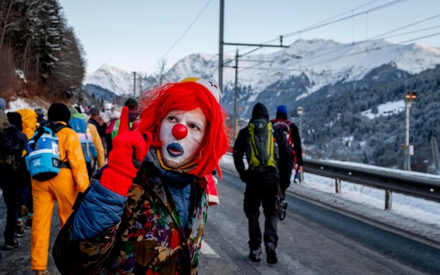 A man dressed as a clown is part of hundreds of climate protesters who are on a three-day protest march from Landquart to Davos pass the city of Klosters, Switzerland, Monday, January 20, 2020. The World Economic Forum will start on Tuesday. (Photo by Michael Probst/AP Photo)