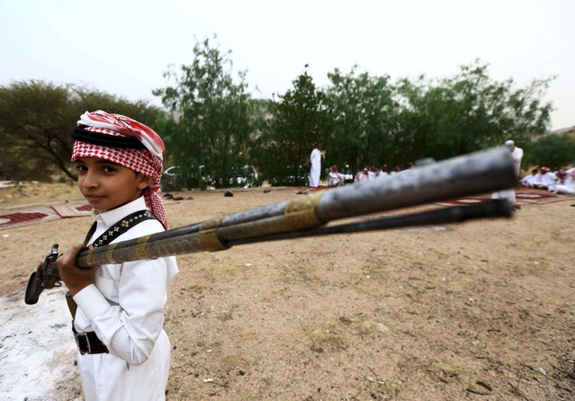 A boy holds a weapon as he poses for a photo during a traditional excursion near the western Saudi city of Taif, August 8, 2015. (Photo by Mohamed Al Hwaity/Reuters)