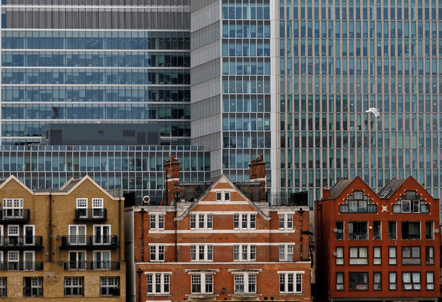 Apartment buildings are backdropped by skyscrapers of banks at Canary Wharf in London, Britain October 30, 2015. (Photo by Reinhard Krause/Reuters)