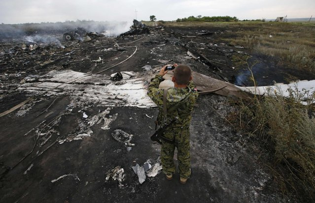 An armed pro-Russian separatist takes pictures at the site of a Malaysia Airlines Boeing 777 plane crash near the settlement of Grabovo in the Donetsk region, July 17, 2014. The Malaysian airliner Flight MH-17 was brought down over eastern Ukraine on Thursday, killing all 295 people aboard and sharply raising the stakes in a conflict between Kiev and pro-Moscow rebels in which Russia and the West back opposing sides. (Photo by Maxim Zmeyev/Reuters)