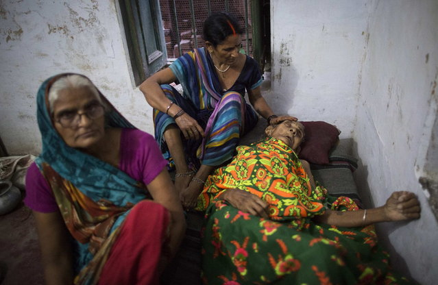 Munna Kuvar, 105, lies on a bed as she is comforted by relatives at Mukti Bhavan (Salvation House) in Varanasi, in the northern Indian state of Uttar Pradesh, June 17, 2014. (Photo by Danish Siddiqui/Reuters)