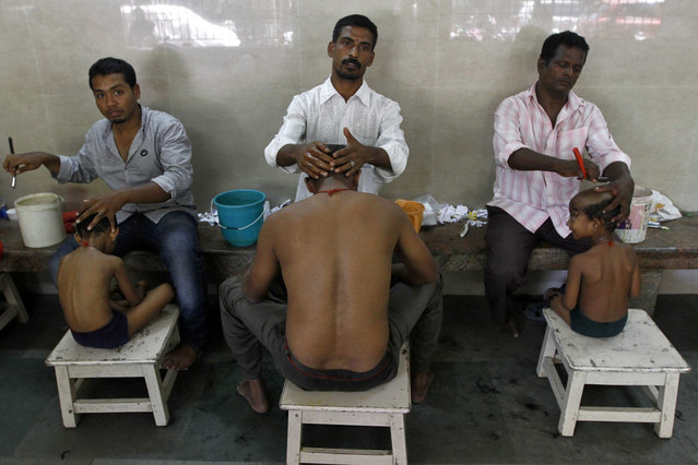 A father (C) and his two sons have their heads shaven as part of a ritual after what they say was fulfilment of their wishes during the Aadi Krithigai festival celebrations at a temple in the southern Indian city of Chennai July 21, 2014. During the festival, Hindu women also fast for the whole day in hope of winning the favour of Lord Muruga. (Photo by Reuters/Babu)