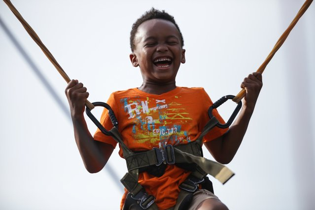 Dominic Bennett,6,  bounces on the bungee trampoline during AthFest in Athens, Ga.,Friday, June 24, 2016. The AthFest music festival is a production of AthFest Educates, a nonprofit music and arts education organization in Athens. (Photo by John Roark/Athens Banner-Herald via AP Photo)