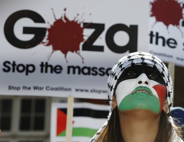 A demonstrator with face painted in the colours of the Palestinian flag protests outside the Israeli Embassy in west London July 26, 2014. Foreign ministers from the United States, Europe and the Middle East called on Saturday for an extension of the 12-hour ceasefire between Israel and Hamas in the Gaza Strip, French Foreign Minister Laurent Fabius said. (Photo by Luke MacGregor/Reuters)