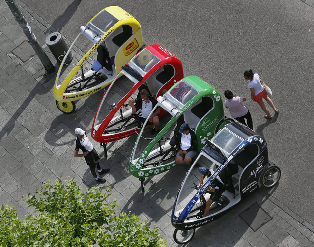 Four colorful bicycle rickshaws wait for customers in central Frankfurt, Germany, Monday, July 10, 2017. (Photo by Michael Probst/AP Photo)