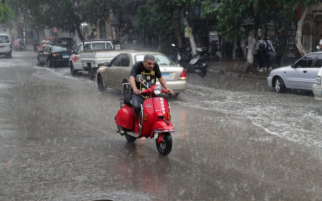 A man rides a motorcycle during rain shower in Cairo, Egypt, 22 October 2019. According to reports, showers are hitting Cairo as temperatures reach 21 degrees Celsius. (Photo by Khaled Elfiqi/EPA/EFE)