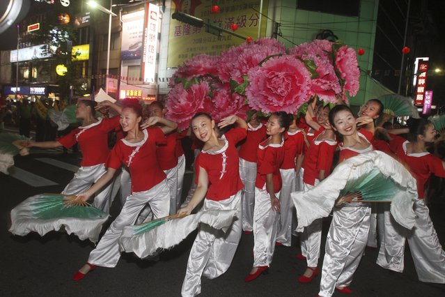 In this photo made late Saturday, August 9, 2014, in Keelung, Taiwan, a traditional Chinese dance troupe performs during a parade marking the beginning of the Chinese folklore's mid-summer's Ghost Month Festival. (Photo by Chiang Ying-ying/AP Photo)