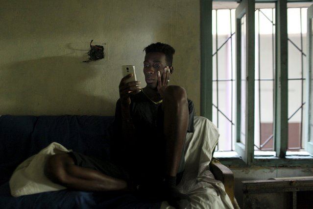 Actor Ramses Pino, 24, looks at his mobile phone prior to taking part in a test to be part of the theatre company Fenix, in Havana, February 10, 2015. (Photo by Alexandre Meneghini/Reuters)