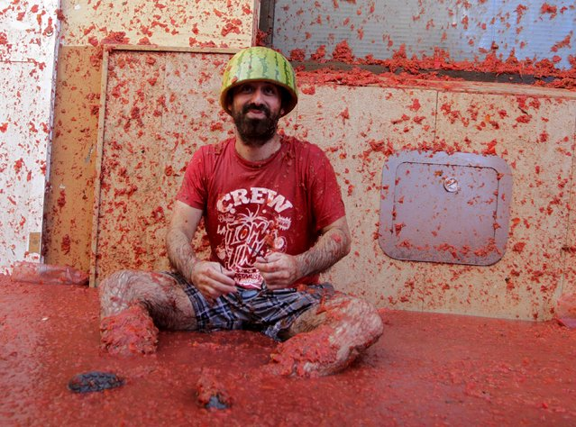 """A reveler covered in tomato pulp rests after the annual """"Tomatina"""" (tomato fight) in Bunol, near Valencia, Spain, August 26, 2015. (Photo by Heino Kalis/Reuters)"""