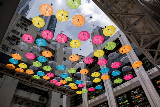 Umbrellas are suspended at the Comix Home Base arts centre in Hong Kong on August 11, 2014. The colourful umbrella canopy was installed to mark the first anniversary of the Comix Home Base, an event space for comic illustrators and animators, and venue for workshops and screenings. (Photo by Alex Ogle/AFP Photo)