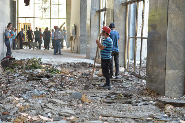 Workers clean up around the damage and debris at the Turkish parliament which was attacked at least three times through the night during a military coup on July 16, 2016 in Ankara, Turkey. Turkish President Recep Tayyip Erdogan has denounced an army coup attempt, that has left high fatalities and thousands injured in overnight clashes in Istanbul and Ankara. (Photo by Erhan Ortac/Getty Images)