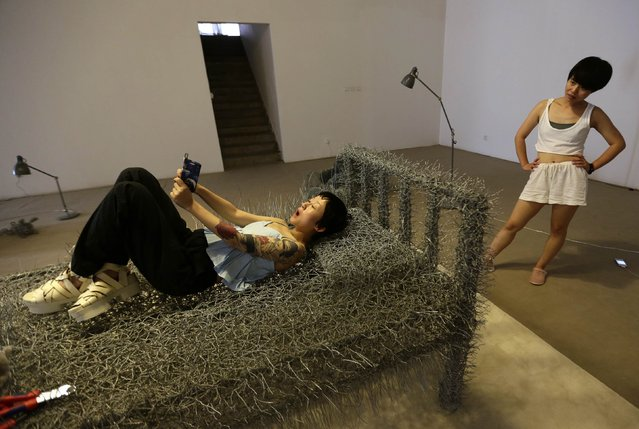 "Chinese artist Zhou Jie (R) looks at her friend who is taking a ""selfie"" on an unfinished iron wire bed, one of Zhou's sculptures, while visiting her at Beijing Art Now Gallery, in Beijing August 11, 2014. (Photo by Jason Lee/Reuters)"