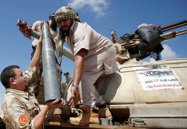 Fighters of Libyan forces allied with the U.N.-backed government carry a tank shell in during a battle with IS fighters in Sirte, Libya, July 21, 2016. (Photo by Goran Tomasevic/Reuters)