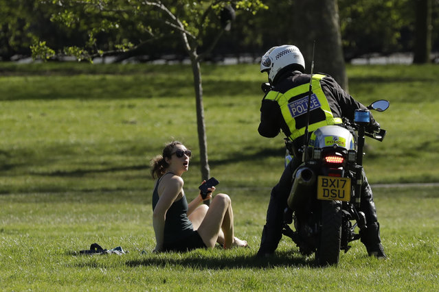 A woman is told to go home by a police officer on a motorbike to stop the spread of coronavirus and keep the park open for people observing the British government's guidance of social distancing, only using parks for dog walking, one form of exercise a day, like a run, walk, or cycle alone or with members of the same household, on Primrose Hill in London, Sunday, April 5, 2020. (Photo by Matt Dunham/AP Photo)