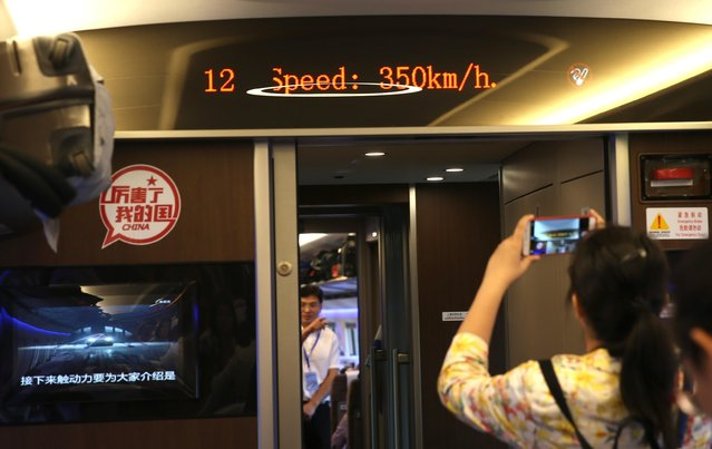 """A passenger takes photos of a screen showing the real-time speed 350 km/h of a """"Fuxing"""" high-speed bullet train on the Beijing-Shanghai Railway (Jinghu Railway) from the Beijing South Railway Station to the Shanghai Hongqiao Railway Station in China on September 21, 2017. Fuxing, China's newest high-speed bullet trains were officially launched between Beijing and Shanghai on Thursday (21 September 2017), at a speed of 350 kilometers per hour. The Fuxing bullet trains were unveiled on June 25 and are capable of a top speed of 400 km/h. The Fuxing has a monitoring system that slows the train in case of emergency or abnormal conditions. Telemetry allows a control center to monitor the train in real time. The Fuxing, which means """"rejuvenation"""", is a substantial upgrade on the Hexie, which means """"harmony"""". The Fuxing is more spacious and energy-efficient, with a longer life expectancy and better reliability. (Photo by Imaginechina/Rex Features/Shutterstock)"""