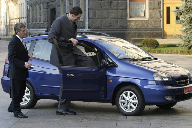 Leonid Stadnyk (R) of Ukraine, named as the world's tallest man by the Guinness World Records, gets into a car as Ukraine's President Viktor Yushchenko watches in Kiev March 24, 2008. Stadnyk, who stands at 2.53 metres (8 feet, four inches), received a car as a present from the president. (Photo by Vladimir Sindeyev/Reuters)