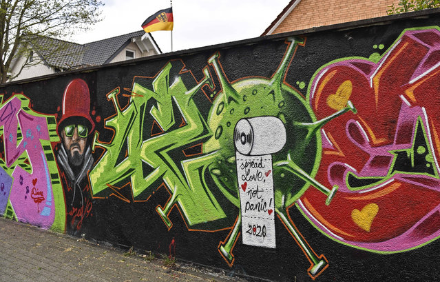 """A graffiti by street artist """"Uzey"""" depicts the coronavirus and the great toilet roll grab with a lettering reading """"spread love, not panic"""" on a wall in Hamm, Germany, on Easter Monday, April 13, 2020. (Photo by Martin Meissner/AP Photo)"""