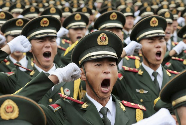 Paramilitary policemen and members of a gun salute team shout slogans at an oath-taking ceremony for the upcoming military parade to mark the 70th anniversary of the end of the World War Two, at a military base in Beijing, China, September 1, 2015. (Photo by Reuters/Stringer)