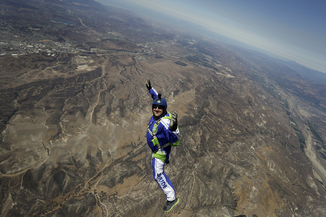 In this Monday, July 25, 2016 photo, skydiver Luke Aikins smiles as he jumps from a helicopter during his training in Simi Valley, Calif. After months of training, this elite skydiver says he's ready to leave his chute in the plane when he bails out 25,000 feet above Simi Valley on Saturday. That's right, no parachute, no wingsuit and no fellow skydiver with an extra one to hand him in mid-air. (Photo by Jae C. Hong/AP Photo)