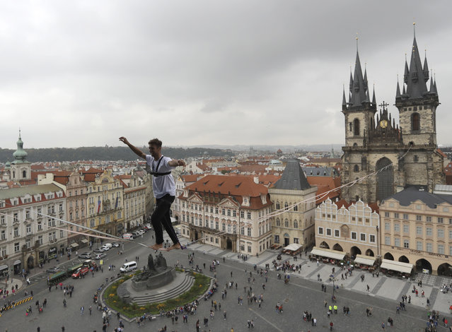 An athlete balances on a slackline stretched across the Old Town Square in Prague, Czech Republic, Monday, September 25, 2017. The performance was part of a campaign supporting people living with diabetes. (Photo by Petr David Josek/AP Photo)