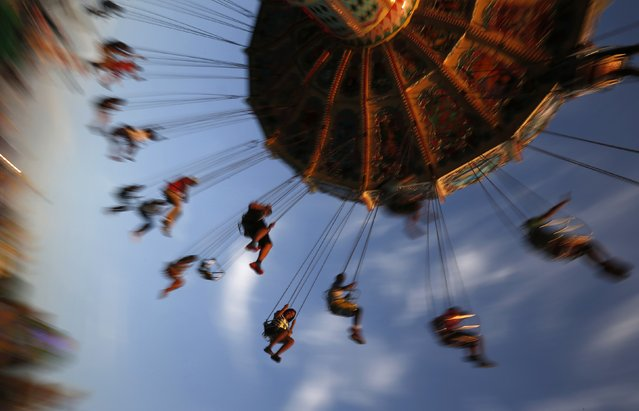 People ride on a swing at the Wisconsin State Fair in West Allis, Wisconsin, August 9, 2014. The fair started over 150 years ago and mixes agricultural exhibits with amusements rides. (Photo by Jim Young/Reuters)