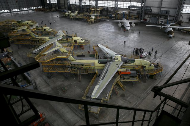 Journalists stand near new Antonov airplanes at the Antonov aircraft plant in Kiev, Ukraine, September 7, 2015. (Photo by Gleb Garanich/Reuters)