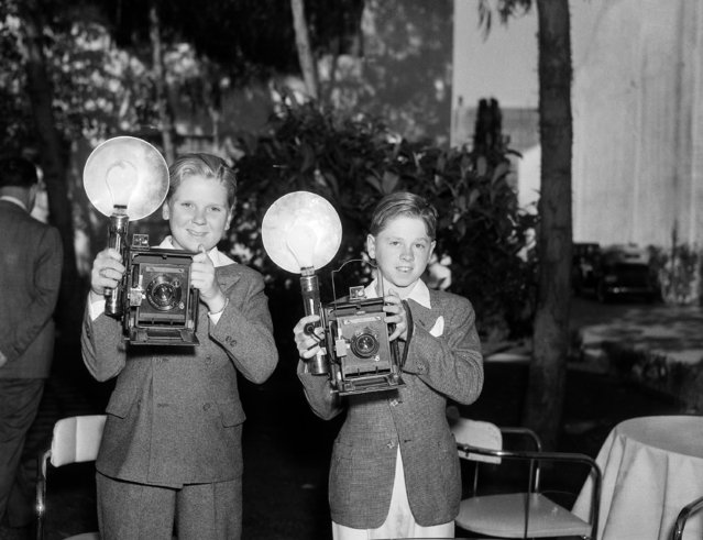 Jackie Cooper, left, and Mickey Rooney, child actors, after an opportunity to use cameras owned by visiting newspaper men, believe they'd rather work behind the lenses instead of in front of them. They are shown in their first attempt at picture taking, June 22, 1935. (Photo by Frank Filan/AP Photo)