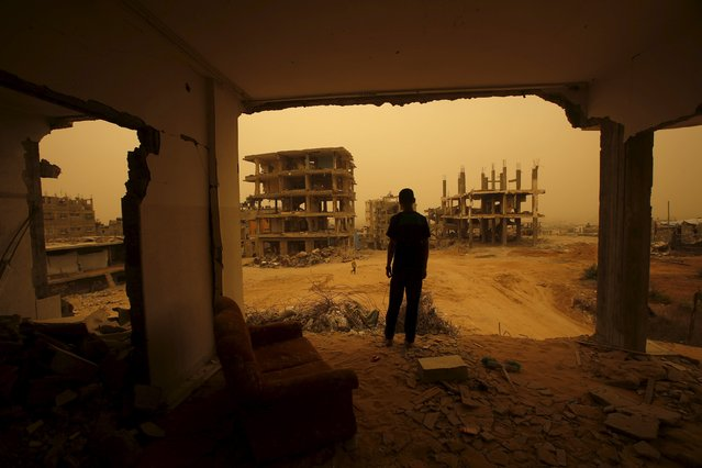 A Palestinian stands inside the remains of a house, that witnesses said was destroyed by Israeli shelling during a 50-day war in 2014 summer, during a sandstorm in Gaza September 8, 2015. (Photo by Suhaib Salem/Reuters)
