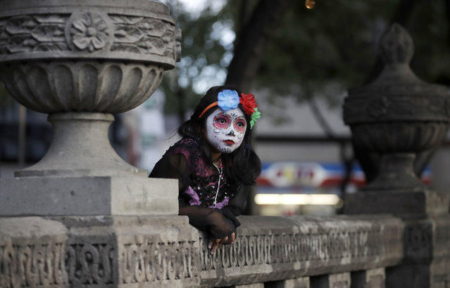 """A girl dressed as Mexico's iconic """"Catrina"""" leans against stone benches as she awaits the start of the Grand Procession of the Catrinas, part of upcoming Day of the Dead celebrations in Mexico City, Sunday, October 22, 2017. (Photo by Rebecca Blackwell/AP Photo)"""