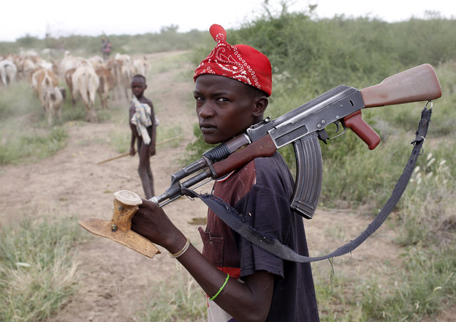 A Turkana boy herds cows as he carries a rifle in north western Kenya near the town of Kibish inside the Turkana region of the Ilemy Triangle September 26, 2014. (Photo by Goran Tomasevic/Reuters)